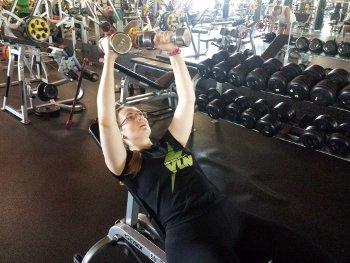Тренировка с гантелями в спортивном зале